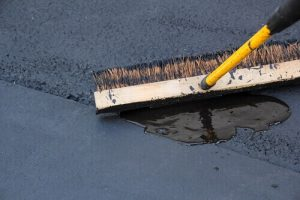 A homeowner applies asphalt sealer with a stiff broom
